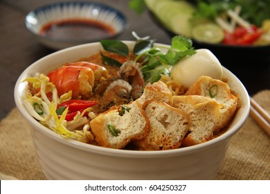 Curry Laksa. Peranakan spicy noodle soup in rich and fragrant curry broth. Served in a ceramic bowl with chili sauce and extra vegetables on side.
