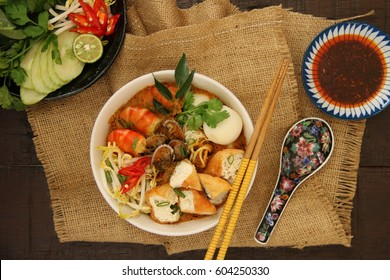 Curry Laksa. Peranakan spicy noodle soup in rich and fragrant curry broth. Served in a bowl with chili sauce and extra vegetables on side. The chopsticks are on the bowl and the spoon laid next to it.