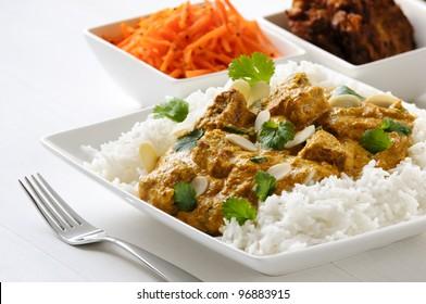 Curry meal - lamb pasanda with rice, bhaji and carrot salad behind.