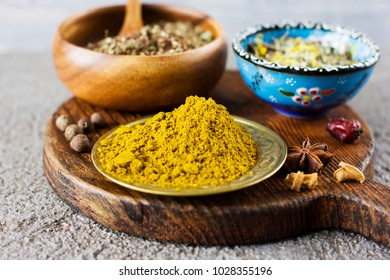 Curry powder and dry spices in bowls on wooden Board on a concrete background