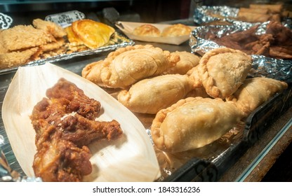 Curry puffs, deep fried chicken wings and other foods on various serving trays in a self-service (buffet) catering occasion. Delicious party finger foods.