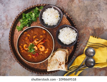 Curry shrimp. Spicy mixture of tomato and masala spices with shrimp.  Served with naan bread and pilau rice on vintage copper tray. Top view, blank space