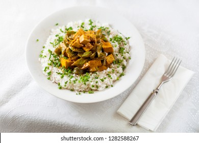 Curry Tofu with green pepper, turmeric coconut milk and onion on rice decorated with chives