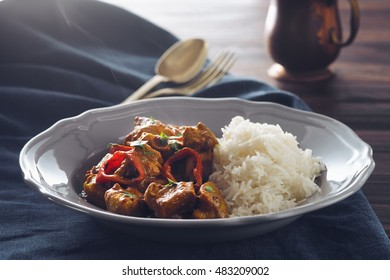 curry turkey with pepper on a blue tablecloth and a dark wooden table
