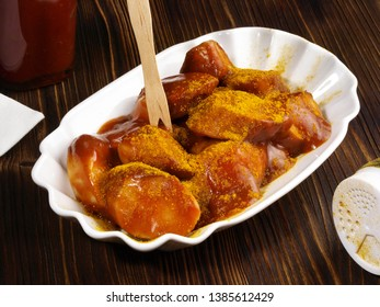 Curry Wurst with Sauce on wooden Background