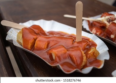 Curry wurst, a typical street food in Berlin, Germany. Sausages and curry sauce, with french fries.