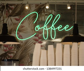 Cursive green neon sign COFFEE in front of palm and flower wallpaper and wood boards behind stacked paper cups and lamps