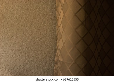 Curtain against a textured bedroom wall. Similar colors, contrast of patterns and style.