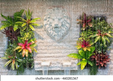 Curtain of interior waterfall / fountain decorated with lion face and colorful plants and ferns on white brick wall.