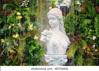 Curtain of interior waterfall / fountain decorated with marble woman statue on a roman pole and colorful plants and ferns.