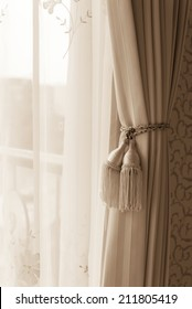 Curtain with curtain tieback at window, selective focus.  Processed with vintage style.