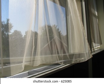 Curtains blowing in the wind a hot summer day.