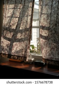 Curtains blowing in the wind from inside view. Photo shot in natural lighting.