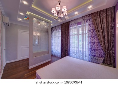 Curtains at the French windows with a big bed and a glass partition