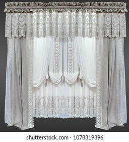 A curtains made of natural flaxen cloth in gray colors with mbroidery and lace trim, with the pelmet and a white tulle.