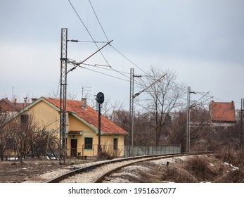 Curve of a railway line, a raildroad track, electrified, on a small local branch line, during a cold grey afternoon in Europe.