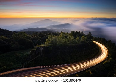 Curve road before sunrise with fog over the mountain