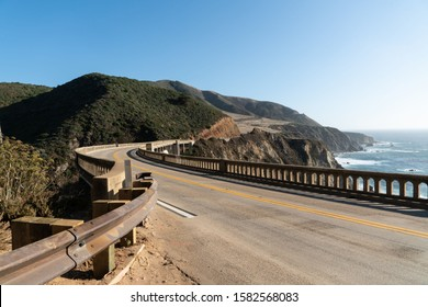Curve In The Road At Big Sur's Bixby Creek Bridge Along The Pacific Coast Highway With Amazing Mountain Views And Ocean Seascapes.