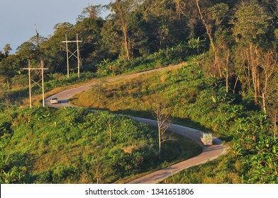 Curve road with car through mountain and forest with sunlight