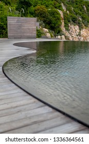 Curve swimming pool with wooden deck outdoor selective focus