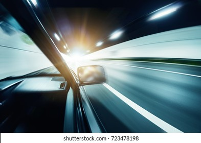 curve tunnel inside and road exit to light with car driving motion blur
