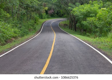 Curve way of asphalt road through the tropical forest in northern Thailand.