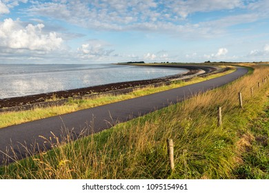 Curved asphalt road on a dike along the water of a Dutch estuary. It is low tide on a sunny day in the summer season.
