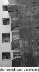 curved balconies and square windows in an old stained concrete apartment building