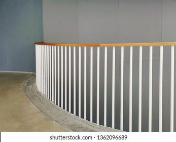 Curved Balcony with White Fencing Rods and Wood Rail