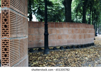 Curved brick wall in city park, focus on foregtround, space for copy