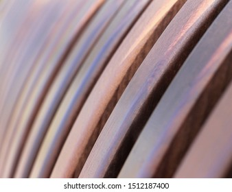 Curved brown wooden slat background, image of a lattice of wooden slats of dark brown color for use as a background. Half-round, openwork design.