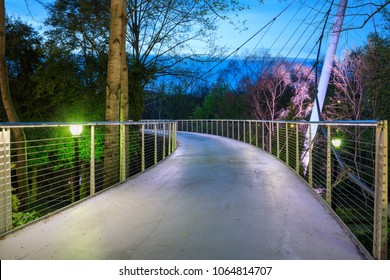 Curved deck of the Liberty pedestrian suspension cable bridge over the Reedy River in Falls Park, downtown Greenville, South Carolina.