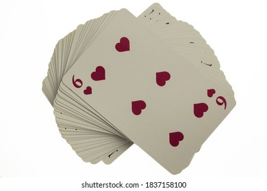 Curved deck of playing cards. Above is a red six. Photographed on a clean white background with clipping