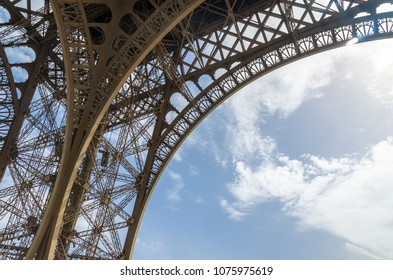 The curved detail of the wrought iron of the Eiffel Tower against against a blue cloudy sky in summer, Paris, France