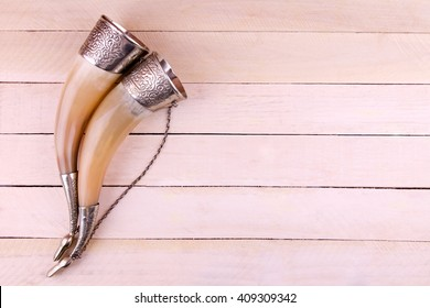 Curved drinking horns on the wooden background
