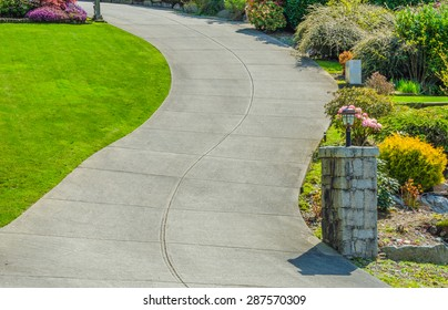 Curved driveway to the building, house with nicely landscaped and trimmed sides.