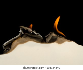 Curved edge of paper burnt and curled on a black background
