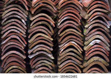Curved edges of neatly stacked pile of old terracotta roof tiles covered in lichen and signs of ageing, ready for recycling or reuse in construction