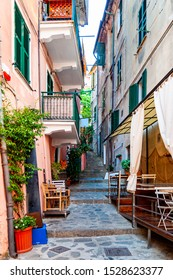Curved elevated stairs street full of outdoor elements like street lanterns, growing plants, balconies and windows telling their stories about the city life in Monterosso Al Mare, Cinque Terre, Italy