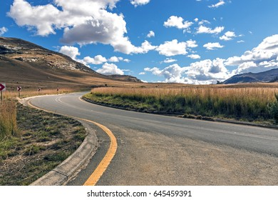 Curved empty rural asphalt road running through dry winter mountain landscape against blue cloud sky horizon n Orange Free State in South Africa