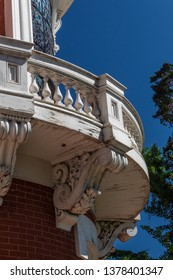 Curved exterior wood balcony with elaborate corbels, vertical aspect