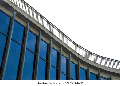 the curved facade of a glass and concrete building, topped by a balcony railing