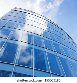 curved facade of modern glass blue office and sky with clouds reflected