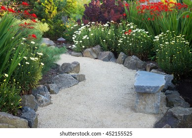 A curved garden path edged with stones winds through a perennial garden with crocosmia and daisies..