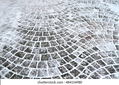 Curved gray cement block pavement with snow