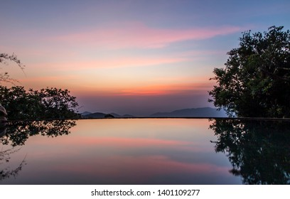 A curved infinity pool on a completely calm night reflects the evening light and silhouetted trees like a perfect mirror. High cloud creates bands of pink and yellow in the blue hour after sunset.