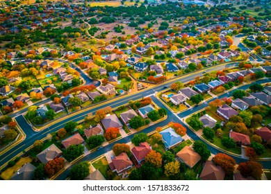 curved modern layout seen from bird's eye view aerial drone view above Suburb neighborhood with fall colors charging leaves and gorgeous colorful landscape above houses and homes