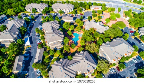 Curved modern swimming pool and bright lush green trees surrounding cozy new development suburb apartment complex townhomes - aerial drone view - Round Rock , Texas , USA