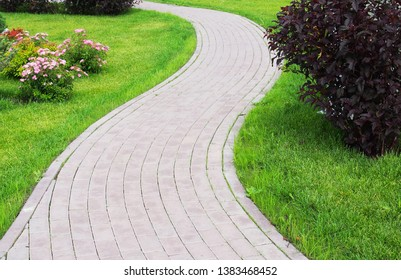 Curved paved with bricks footpath running ahead along a green grassy lawn. Landscaping design