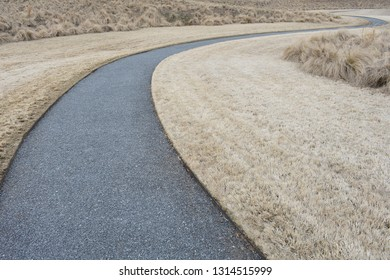 Curved paved path disappearing around a corner in dry grass.
